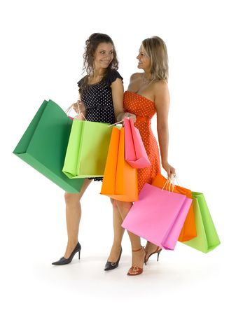 Two beautiful, young woman standing and holding bags. First woman is showing something in hers bag. Both woman are looking at each other. Isolated on white in studio. Whole body photo