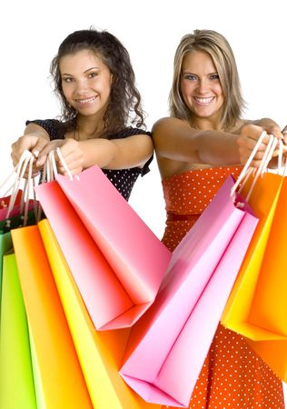 Two beautiful, young woman standing and holding bags. Womans are giving bags to somebody. White background, looking at camera photo