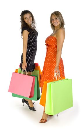 Two beautiful, young woman standing and holding bags. Looking at camera, isolated on white in studio. Whole body photo