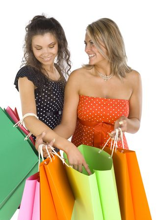 18 19: Two beautiful, young woman standing and holding bags. First woman is showing something in bag.  Second woman is looking at hers friend. White background