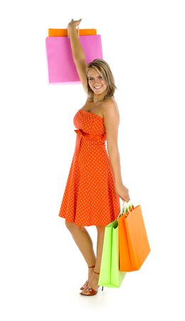 Young, beautiful woman standing and holding bags. Smiling and looking at camera. Isolated on white in studio. One hand up, whole body photo