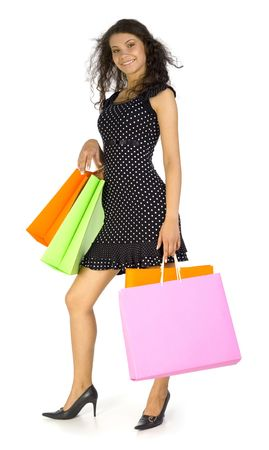 18 19: Young, beautiful woman standing and holding bags. Smiling and looking at camera. Isolated on white in studio, whole body Stock Photo