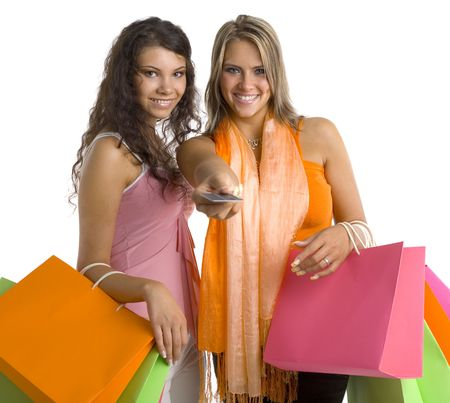 Two, beautiful woman standing and holding bags. One is giving credit card. They are smiling and looking at camera. White background Stock Photo - 1290331