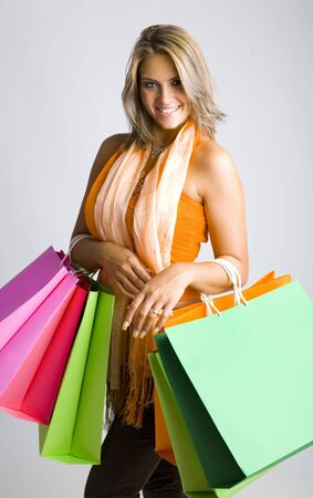 18 19: Young, beautiful woman holding bags. Smiling and looking at camera. Gray background Stock Photo