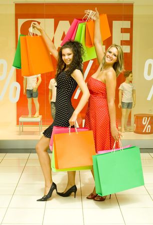 Two, beautiful woman standing in big shop, holding bags and smiling. Looking at camera, whole body Stock Photo - 1290352