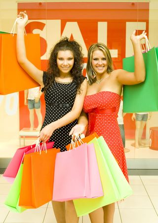 18 19: Two, beautiful woman standing in big shop, holding bags and smiling. Looking at camera, whole body Stock Photo