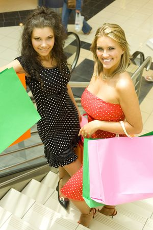 Two, beautiful woman standing on stairs in big shop. Holding bags and looking at camera photo