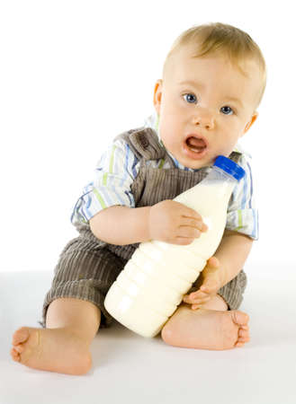 Little baby boy sitting on the floor, looks confused. Holding a bottle of milk. Looking at camera photo