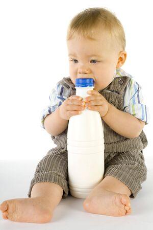 poco: Poco niño sentado en el suelo. Holding y mordiendo una botella de leche. Todo el cuerpo Foto de archivo