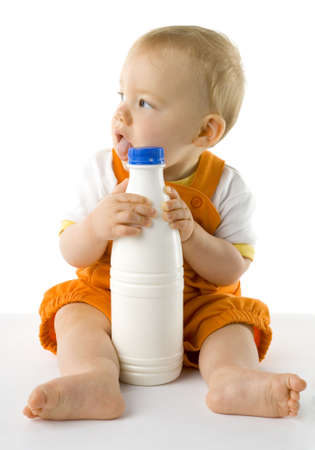 plactic: Little baby boy sitting on the floor and holding a bottle of milk. Whole body, front view