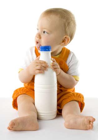 Poco niño sentado en el suelo y la celebración de una botella de leche. Todo el cuerpo, la vista frontal