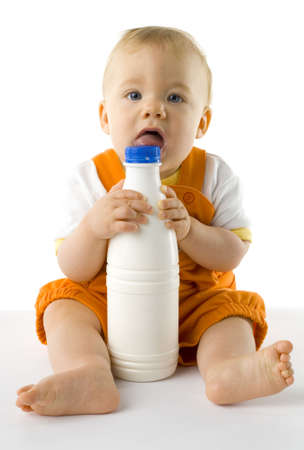 plactic: Little baby boy sitting on the floor. Holding and biting a bottle of milk. Looking at camera, whole body. Front view