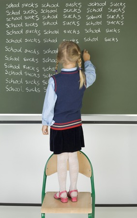 Little girl standing on chair in front of blackboard. Writing on it. Rear view, whole body