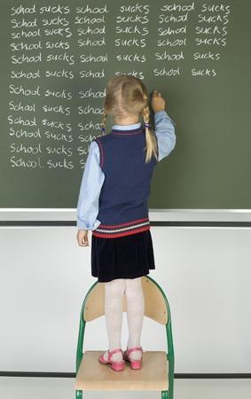 school uniform girl: Little girl standing on chair in front of blackboard. Writing on it. Rear view, whole body