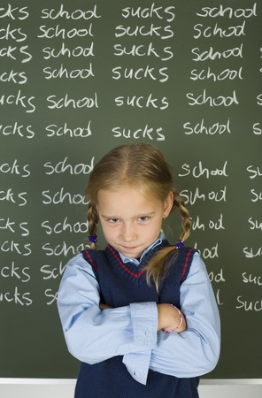uniform student: Little, angry girl standing in front of blackboard with crossed arms. Looking at camera. Front view