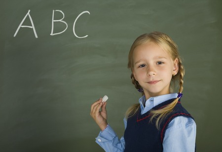 uniform student: Little, pretty girl standing in front of blackboard. Holding chalk. Smiling and looking at camera