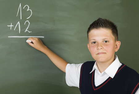 grade schooler: Young boy standing in front of blackboard and writing. Smiling and looking at camera. Front view