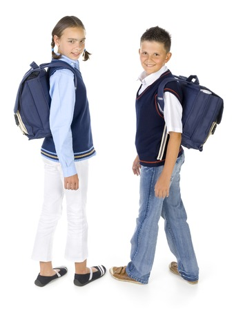Portrait of boy and girl. Theyre looking at camera and smiling. Holding backpacks. Isolated on white in studio, side view Stock Photo