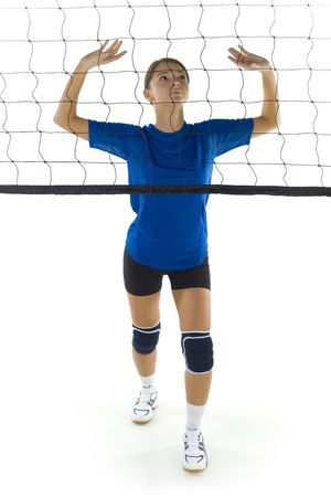 Young, beauty volleyball player. Standing in front of net and preparing to take the ball. White background. Whole body, front view photo
