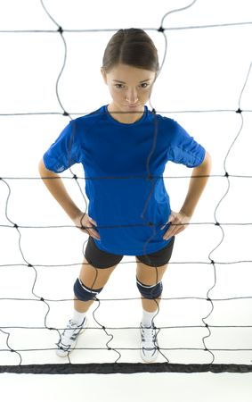 Young, beauty volleyball player. Standing in front of net and preparing to take the ball. White background. Whole body, high angle view photo
