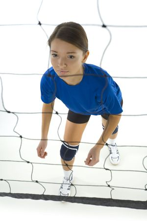 Young, beauty volleyball player. Standing in front of net and preparing to take the ball. White background. Whole body, high angle view Stock Photo - 2605874