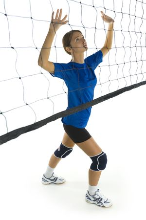 emulate: Young, beauty volleyball player. Standing in front of net and preparing to take the ball. White background. Whole body, side view