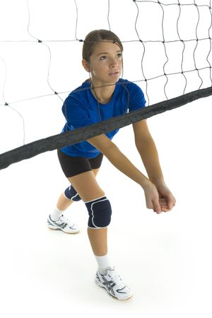 the whole body: Young, beauty volleyball player. Standing in front of net and preparing to take the ball. White background. Whole body, side view