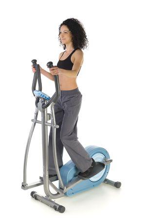 eliptica: Joven mujer en el ejercicio de bicicleta el�ptica. Ella  's sonriendo y buscando en alguna parte. Aislado en fondo blanco.