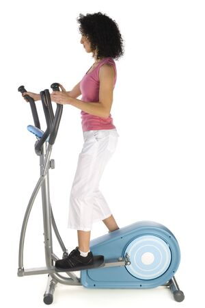 sportingly: Young woman exercising on elliptical bike. Side view, isolated on white background.