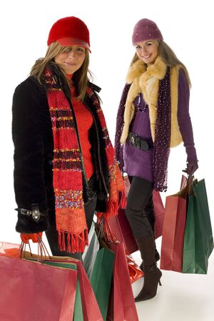winter couple: Two young women with shopping bags. Theyre smiling and looking at camera. Front view. Stock Photo