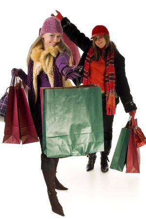 Two happy women with shopping bags. Looking at camera, front view. White background. photo