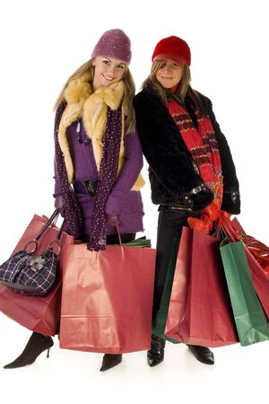 Two young women with shopping bags. They're smiling and looking at camera. Front view, white background. Stock Photo - 2606085