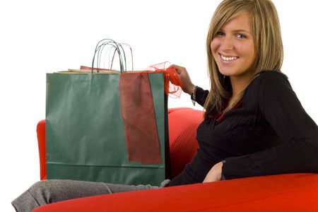 Young, happy woman sitting on couch with shopping bags. Looking at camera, side view. White background. photo