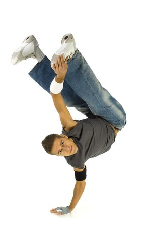 causal: Young bboy standing on one hand. Holding legs in air. Looking at camera. Isolated on white in studio. Front view, whole body Stock Photo
