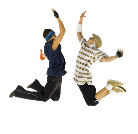 causal: Two bboys freezed in jump. Trying to give high five. Isolated on white in studio. Side view, whole body