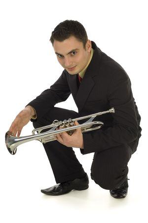muscian: Hombre en el juego que sostiene una trompeta y que se agacha. C�mara fotogr�fica sonriente y que mira de He en. Aislado en el fondo blanco.