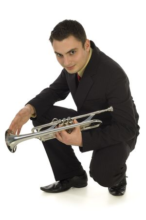 muscian: Man in suit holding a trumpet and crouching. Hes smiling and looking at camera. Isolated on white background.