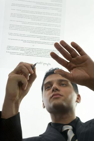Young, serious businessman signing centract. Low angle view Stock Photo - 2605986