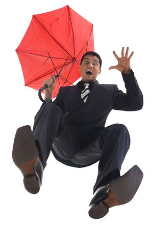 Young, screaming businessman with umbrella. He looks like he is falling. looking at camera. Low angle view photo