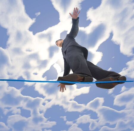 Young businessman walking on line in the air. Holding balance. Low angle view photo