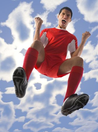 Young, screaming football player with closed eyes and clenched fists. Low angle view Stock Photo - 2605977