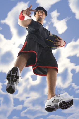 sportingly: Young, confident and smiling basketball player. Pointing and looking at camera. Holding ball. Low angle view