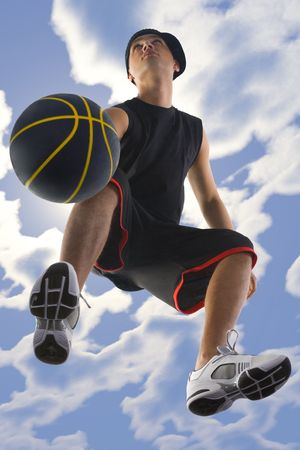 Young basketball player dribbling ball. Looking at something. Low angle view photo
