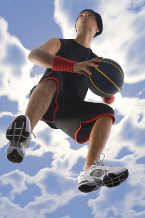Young basketball player with ball in action. Looking at something. Low angle view photo