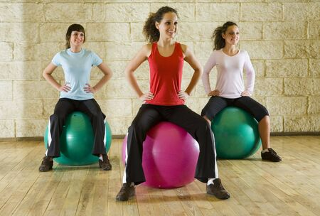 sportingly: A group of women making exercise sitting on big balls and holding hands on hips. Front view. Stock Photo