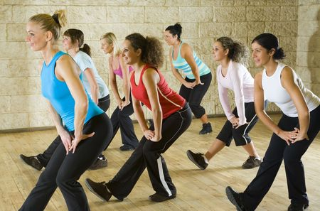 sportswoman: A group of women exercising in the fitness club. Focus on the woman in red shirt. Side view.
