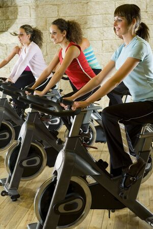 sportingly: The group of women training on exercise bikes at the gym. Side view.