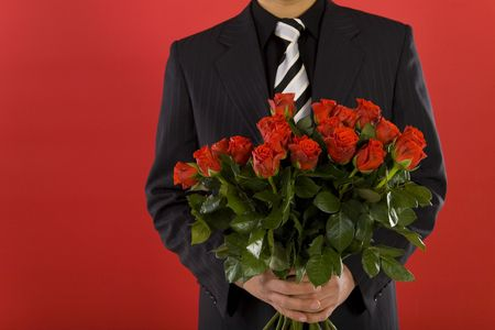 Businessman with bouquet of roses in hands. We dont see his face. Front view