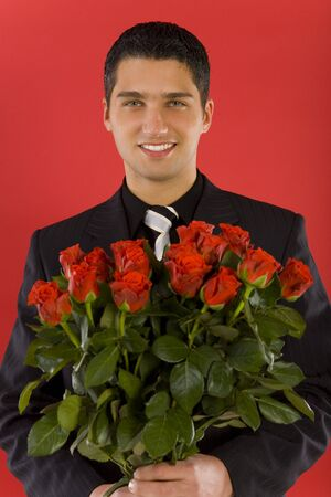 Handsome businessman with bouquet of roses in hands. Smiling and looking at camera. Close up on face. Front view Stock Photo - 2610452