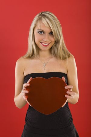 Beautiful woman in black dress, holding heart-shaped box of chocolates. Smiling and looking at camera. Front view  Stock Photo - 2610482